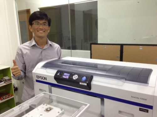 Koh standing beside his company's Epson SureColor printer
